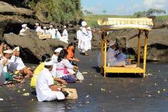 Balinese Hindoese priesters die rond iconische Pura Tanah Lot bidden stock afbeelding