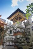 Balinese Hindu family shrine or temple ornately covered with gold showing many effigies of gods and demons. Photographed in vertical format royalty free stock images