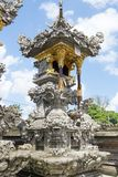 Balinese Hindu family shrine or temple ornately covered with gold showing many effigies of gods and demons. A section of a typical high class Balinese Hindu royalty free stock photo