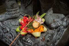 Balinese-Hindu offerings are left for the Gods at a stone-carver's workshop in Ubud, Bali, Indonesia Stock Images