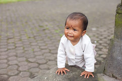 Balinese infant. BALI - JANUARY 22. Infant crawling at the Mother Temple in Besakih on January 22, 2012 in Bali, Indonesia. Most Balinese hindus families make a Stock Image