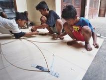 Balinese-Jungen, die einen traditionellen Drachen machen Lizenzfreie Stockfotos