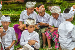 Balinese kids with cellphones. Group of young Indonesian boys wearing traditional Balinese clothes, focused on their cellphones, in Ubud, Bali, Indonesia Royalty Free Stock Image