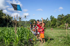 Balinese kids with kites. Bali, Indonesia - July 07, 2015: Balinese kids playing with kites in the fields royalty free stock photography