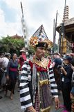 Balinese man dressed in traditional costume walks in procession in Ubud, Bali during the Royal family funeral 2nd March 2018. Balinese man dressed in traditional Royalty Free Stock Images