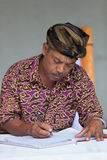 Balinese man maintain records in register book Stock Photos