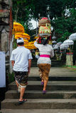 Balinese man and woman going to the temple, Ubud, Bali. Ubud, Indonesia -March 02, 2016: Balinese man and woman in traditional clothes  going to the temple Royalty Free Stock Photography