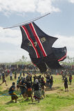 Balinese men try to catch big traditional kite Stock Image