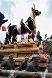 Balinese men carry the black bull sarcophagus during a procession for `Ngaben`, a cremation ceremony at Ubud, Bali, 2nd March 2018. Balinese men working as a Stock Images