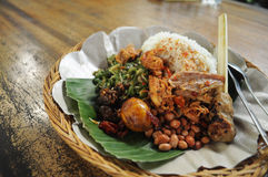 Balinese Mixed Rice. Or in Indonesia called as nasi campur a la Bali usually consists of vegetable, egg, tempe, roasted peanut, chicken and sate lilt (fish Royalty Free Stock Photography