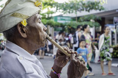 Balinese old man playing flute Stock Photo