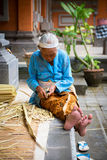 Balinese old women make baskets for offerings Royalty Free Stock Photo