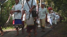 Balinese optocht die naar tempel door bosweg met kleurrijke vlaggen gaan stock video