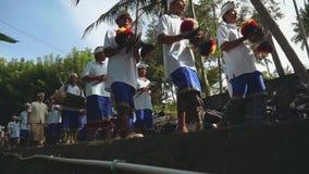 Balinese optocht die naar tempel en speelmuziek, lage hoek gaan stock footage