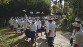Balinese optocht die naar tempel met paraplu's en muzikale instrumenten, hoge hoek gaan stock footage