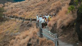 Balinese people in ceremony clothes walking from Pura Batu Korsi hill temple stock video