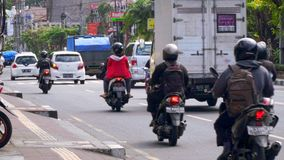 Balinese people navigate motorbikes and other traffic through busy streets. stock video