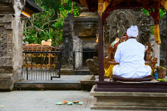 Balinese priest on a religious ceremony. Balinese unrecognizable priest dressed in white clothes in Hindu temple during a religious ceremony, Bali, Indonesia Royalty Free Stock Photos