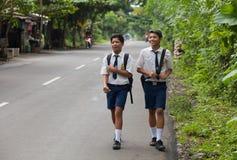Balinese school kids. BALI - JANUARY 24. Balinese school kids in uniform walking home on street in Bali on January 24, 2012 in Bali, Indonesia. Uniforms are worn Royalty Free Stock Photos