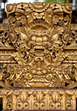 Balinese sculpture. Balinese wooden sculpture of mask dragon face with golden paint Stock Photography