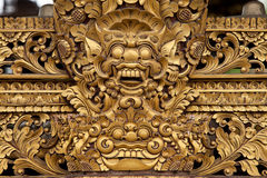 Balinese sculpture. Balinese wooden sculpture of mask dragon face with golden paint Stock Images