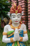 Balinese sculpture with red flower in garden in Lovina, Bali. In Royalty Free Stock Photos