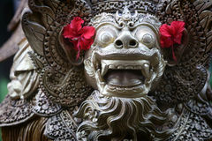 Balinese statue with hibiscus flower Stock Images