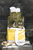 Balinese statue. Stone statue and offering in Bali, Indonesia Stock Photos