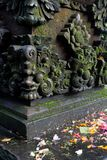 Balinese stone carving with flower petals Stock Photos