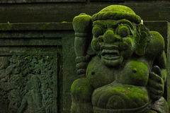 Balinese stone statue covered with moss Royalty Free Stock Photography