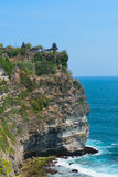 Balinese temple on rock above blue tropical sea Stock Photography