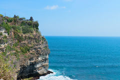 Balinese temple on rock above blue tropical sea Stock Photos