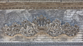 Balinese temple wall with traditional guard demon head Stock Images