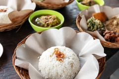 Balinese traditional lunch, rice and other dishes. On top of wooden table royalty free stock images