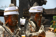 Balinese traditional Sculptures with red faces and white bandana Stock Images