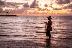 Balinese visser die op een strand bij zonsopgang vissen Stock Foto's