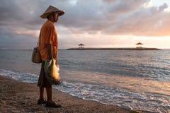 Balinese visser die op een strand bij zonsopgang vissen Stock Foto