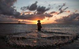 Balinese visser die op een strand bij zonsopgang vissen Stock Afbeelding