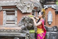Balinese vrouw die dienstenaanbod in tempel zetten royalty-vrije stock afbeelding
