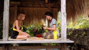 Balinese vrouw die Kaukasische vrouw tonen hoe te om dienstenaanbod te maken stock video