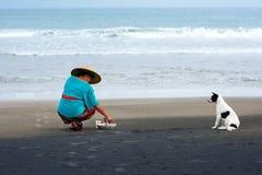Balinese vrouw op een vulkanisch Strand die dagelijks op aard-gebaseerde verering van Balinees Hindoeïsme maken Canggu, Bali, Ind Stock Afbeeldingen