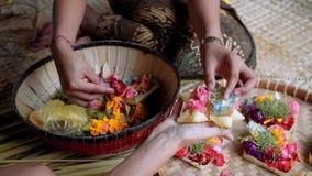 Balinese vrouwen die dienstenaanbod Canang Sari maken stock videobeelden