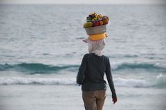 Balinese woman carrying a basket of fruits on her head. Bali is an Indonesian island Stock Photo
