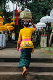 Balinese woman carrying ceremonial box with offerings on her head, Ubud Royalty Free Stock Image