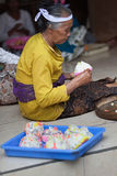 Balinese woman makes sweets for offerings Royalty Free Stock Image