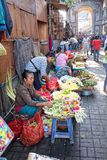 Balinese woman in market sell flower petals for everyday offering Royalty Free Stock Images