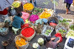 Balinese woman in market sell flower petals and fruits for everyday offering Stock Image