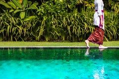 Balinese woman walking on the pool edge. Balinese woman in traditional dress walking on the pool edge Royalty Free Stock Photo