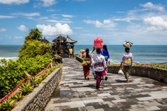 Balinese women carrying baskets with offerings to a temple at Pura Tanah Lot, Bali Island, Indonesia Royalty Free Stock Image