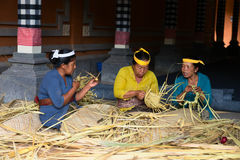 Balinese women make baskets for offerings Stock Photo
